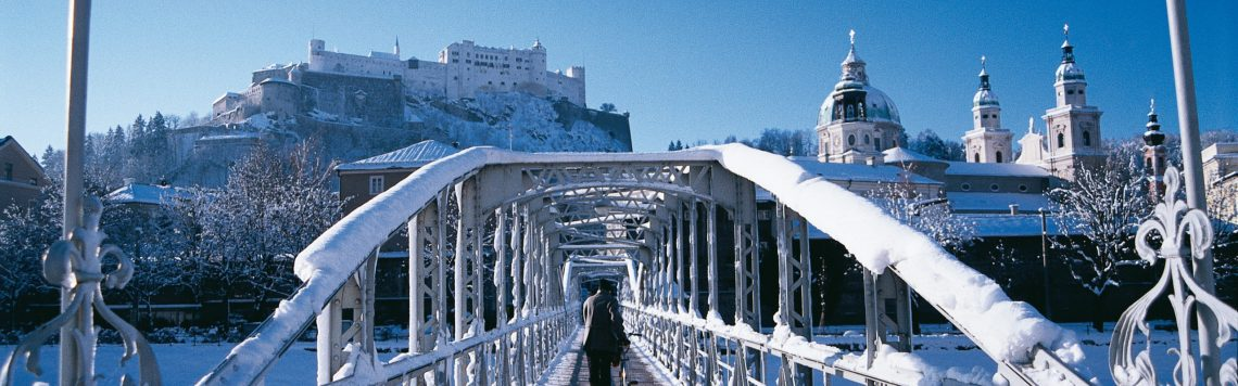 Verschneiter Mozartsteg mit Altstadt und Festung Hohensalzburg. Mozart bridge in winter with view to the historic city center of Salzburg.